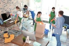 Команда привратников в равномерном офисе чистки стоковое фото
