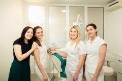 Команда профессионалов в зубоврачебной клинике, представляя около оборудования стоковое изображение rf