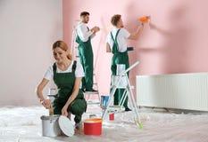 Команда профессиональных оформителей крася стену Домашние ремонтные услуги стоковое фото