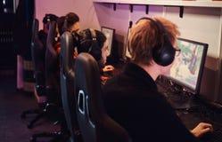 Команда профессиональных sportmans кибер, поездов для чемпионата, игр в предназначенной для многих игроков видеоигре на ПК в игре стоковая фотография