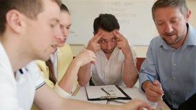 Команда работников офиса обсуждая на творческом проекте в зале заседаний правления Группа в составе молодая деятельность сотрудни сток-видео
