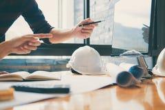 Команда рук инженерства или архитектора конструкции работая на осмотре светокопии в рабочем месте, чертеже и делая эскиз к встреч стоковое изображение