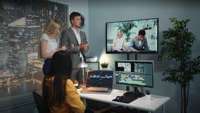Команда смешанной гонки видеоредакторов слушая главное комментируя видео наблюдаемое на большом экране сток-видео