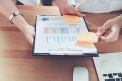 команда совместно работая Современные столы рабочего места и компьютеры, документы изображают диаграммой стоковые фото