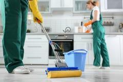 Команда уборки на работе в кухне стоковая фотография