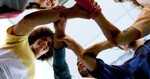 Команда усмехаясь график-дизайнеров формируя стог руки