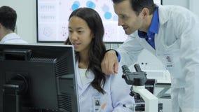 Команда ученых медицинского исследования работает на компьютерах в современной лаборатории видеоматериал