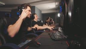 Команда gamers эмоционально радуется в победе играя в клубе e-спорта видеоматериал