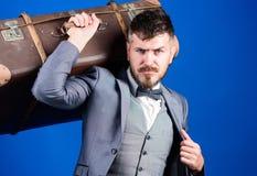 Командировка с ретро чемоданом стильный esthete с винтажной сумкой Бородатый человек в официально костюме мешок тяжелый возмужало стоковые фотографии rf