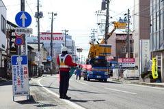 Командир направляет движение для ремонтировать дорогу в городе Фукусимы, Японии Стоковое фото RF