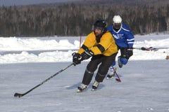 Команды ` s людей состязаются в фестивале хоккея пруда в Rangeley стоковые фотографии rf