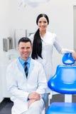 Команда дантиста на зубоврачебной клинике 2 усмехаясь доктора на их работе Стоковые Изображения RF