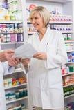 Команда аптекарей взаимодействуя о рецепте Стоковые Изображения RF