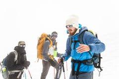 Команда альпинистов приведенных гидом обсуждает предстоящее восхождение стоковое изображение rf