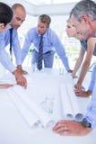Команда бизнесменов смотря план строительства Стоковое фото RF