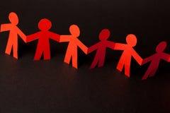 Команда бумажных людей куклы держа руки Стоковые Изображения RF