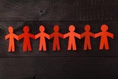 Команда бумажных людей куклы держа руки Стоковые Изображения