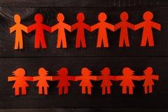 Команда бумажных людей куклы держа руки Стоковое Изображение