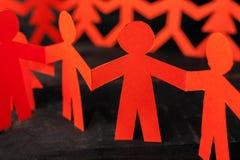 Команда бумажных людей куклы держа руки Стоковые Фотографии RF