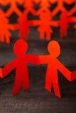 Команда бумажных людей куклы держа руки Стоковая Фотография RF