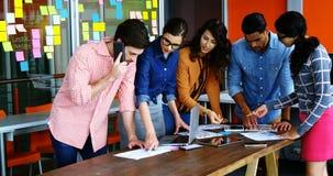 Команда график-дизайнеров обсуждая в встрече видеоматериал