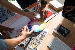 Команда график-дизайнеров обсуждая над документом Стоковые Изображения RF