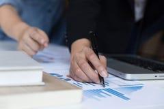 Команда дела анализируя диаграммы и диаграммы дохода с современным подолом Стоковая Фотография