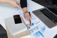 Команда дела анализируя диаграммы и диаграммы дохода с современным подолом Стоковые Изображения