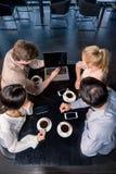 Команда дела на встрече обсуждая проект с компьтер-книжкой в кафе Стоковое Изображение