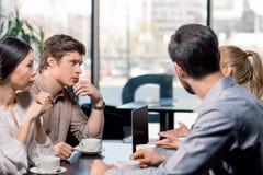 Команда дела на встрече обсуждая проект с компьтер-книжкой в кафе Стоковые Изображения