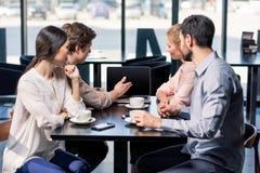 Команда дела на встрече обсуждая проект с компьтер-книжкой в кафе Стоковое фото RF