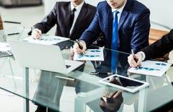 Команда дела обсуждая новый финансовый план компании в рабочем месте Стоковые Фото