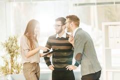 Команда дела обсуждая рабочие планы в лобби современного офиса Стоковое фото RF