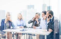 Команда дела при smartphones имея переговор Стоковая Фотография