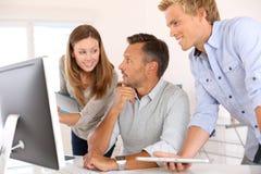 Команда дела работая вместе с компьютером Стоковое фото RF