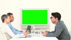 Команда дела смотря белый экран и говорить акции видеоматериалы