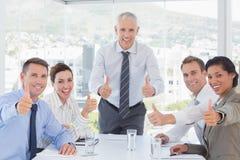 Команда дела усмехаясь на камере показывая большие пальцы руки вверх Стоковое Фото