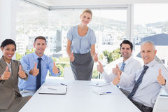 Команда дела усмехаясь на камере показывая большие пальцы руки вверх Стоковые Фото