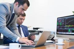 Команда дела удаленно разрешая проблему на деловой встрече используя портативный компьютер и сенсорную панель Стоковые Фото