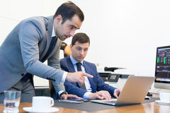 Команда дела удаленно разрешая проблему на деловой встрече используя портативный компьютер и сенсорную панель Стоковое Изображение RF