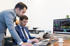Команда дела удаленно разрешая проблему на деловой встрече используя портативный компьютер и сенсорную панель Стоковое Изображение