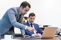 Команда дела удаленно разрешая проблему на деловой встрече используя портативный компьютер и сенсорную панель Стоковые Изображения