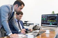 Команда дела удаленно разрешая проблему на деловой встрече используя портативный компьютер и сенсорную панель Стоковое фото RF