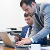 Команда дела удаленно разрешая проблему на деловой встрече используя портативный компьютер и сенсорную панель Стоковые Фотографии RF
