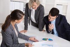 Команда дела человека и женщины сидя вокруг таблицы говоря к стоковое изображение