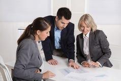 Команда дела человека и женщины сидя вокруг таблицы говоря к стоковое фото