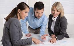 Команда дела человека и женщины сидя вокруг таблицы говоря к стоковое изображение rf