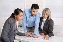 Команда дела человека и женщины сидя вокруг таблицы говоря к стоковые фотографии rf
