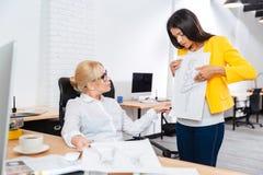 Команда 2 женских архитекторов обсуждая эскизы на офисе Стоковое Фото