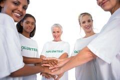 Команда женщины вызывается добровольцем с руками совместно усмехаясь на камере Стоковое Фото